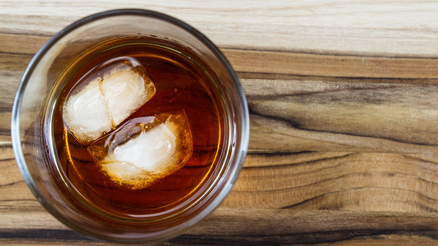 A glass of bourbon with two ice cubes.